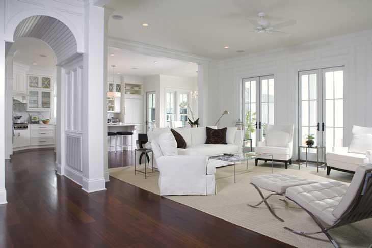 Просторная белая гостиная в классическом стиле. Деревянный паркет на полу