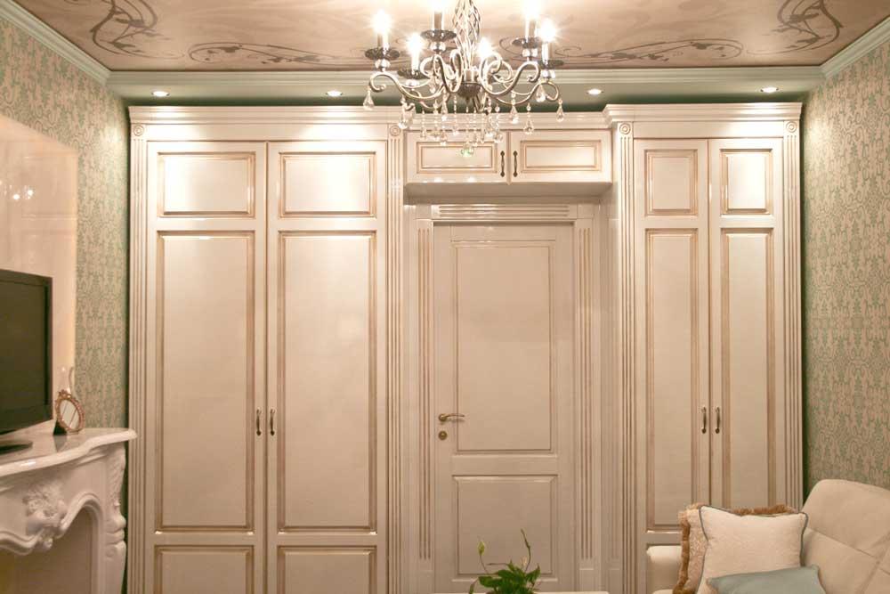 Белый платяной шкаф в классической гостиной. Фото